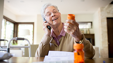 Senior at home reading her prescription bottle to someone over the phone