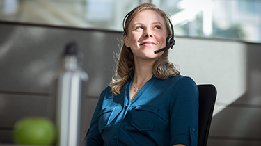 Employee sitting at her desk chair wearing a headset smiling and looking up