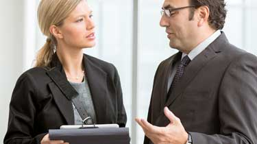 a male and female business professional conversing