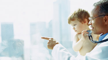 Image of a doctor holding a young child, looking out the window together and pointing at something in the distance