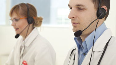 A man and woman caregiver with headsets coaching patients