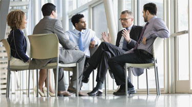 Business professionals seated in a circle and chatting
