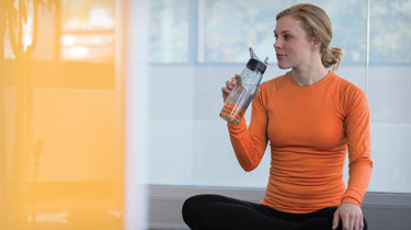 Woman sitting on the floor in workout clothes drinking water from a water bottle