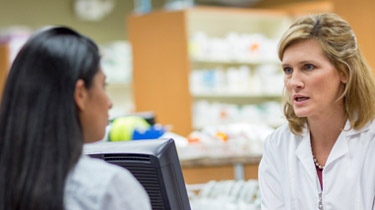 Health care professional speaking to a pharmacist at the counter