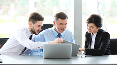 Three business professionals looking at information on a laptop