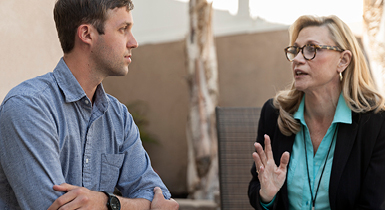 A female professional speaking with a young adult male