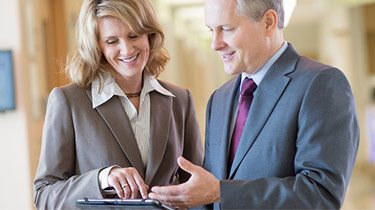Two business professionals looking at information on a mobile device together