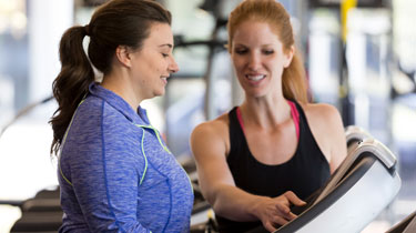 Woman showing another woman how to use a fitness machine
