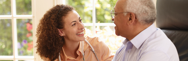 Health care professional wearing a stethoscope speaking to a senior patient at home