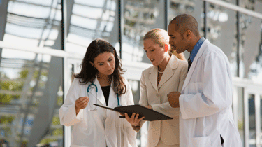 Three medical professionals discussing information in a notebook
